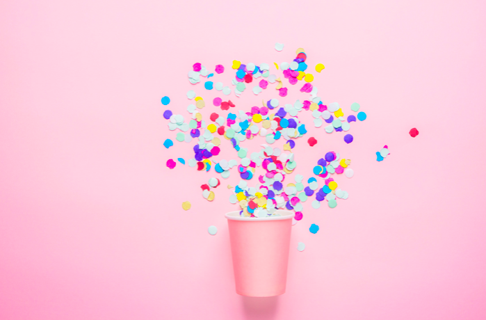 Pink background with a pink cup with confetti coming out of it