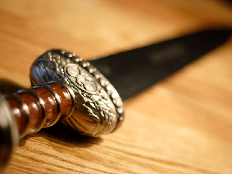 Ornate handle of a sword on a wooden table